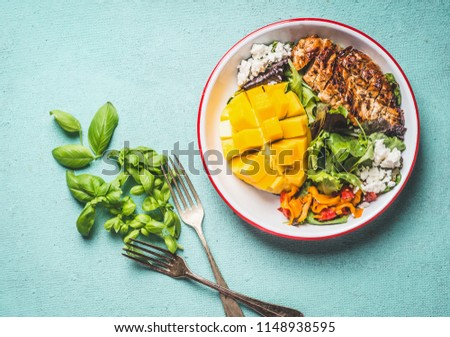 Tasty summer salad with roasted chicken breast and mango in bowl with cutlery on light blue background, top view. Healthy low carb lunch Foto stock ©