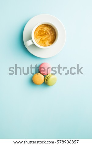 Shutterstock Tasty sweet macarons and coffee cup. Macaroons on blue background. Top view.