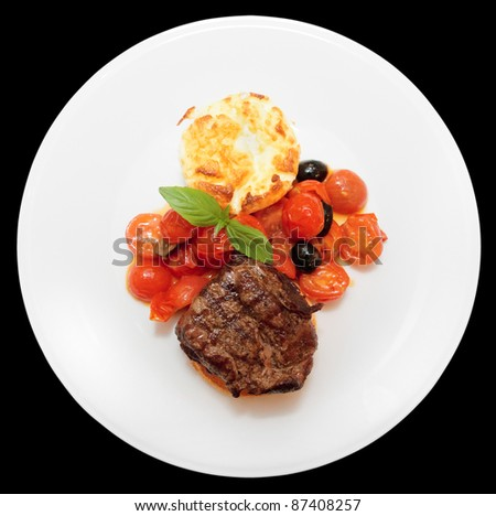 Tasty tenderloin steak with vegetables isolated on black background
