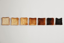 Tasty toasted slices of bread from unroasted to burnt. Stages of toastiness. Selective focus. Crusty delicious snack. White background. Set of toasts each toasted for longer time, degree of roasting.