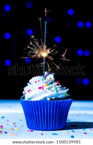 Tasty vanilla cupcake with whipped cream and colorful sprinkles brigade over blue spheres rain plus silver rain candle Stock fotó ©