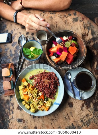 Tasty vegan food on the wooden table in Bali island. Included fresh fruit salad, vegan curry with cashew nuts and red rice, mango sorbet with mint and balinese cup of coffee. #1058688413