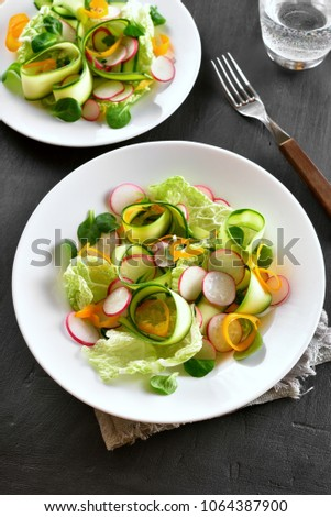 Tasty vegetable salad from zucchini, radish, greens. Top view #1064387900