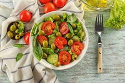 Tasty vegetable salad with fork on kitchen table