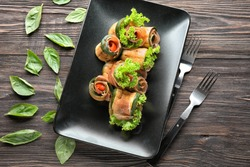 Tasty zucchini rolls with prosciutto on plate