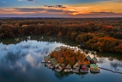 Tata, Hungary - Beautiful autumn sunset over wooden fishing cottages on a small island at Lake Derito (Derito-to) in October. Aerial panorama