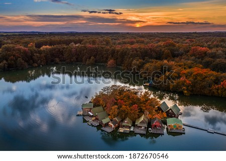 Tata, Hungary - Beautiful autumn sunset over wooden fishing cottages on a small island at Lake Derito (Derito-to) in October. Aerial panorama Сток-фото ©