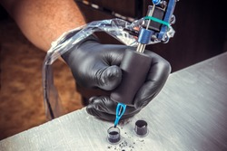 Tatoo artist working with a tatoo machine with black gloves on and use a black inks for tatooing at the tatoo salon closeup/particulars of  tattoo profession/ professional tools for tatooing