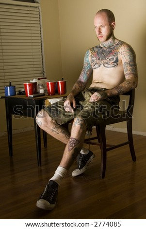 Tatooed male watching TV