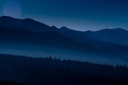 Tatra Mountains and the hills at night. The valleys are hidden in the fog, silhuettes of the trees can be seen from the shadows. Selective focus on the ridge, blurred background.