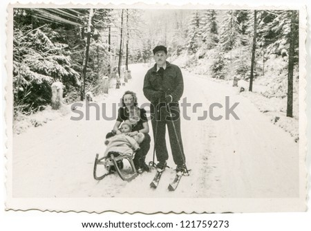 TATRAS MOUNTAINS, POLAND, CIRCA 1954 - Vintage photo of skier posing with her wife and little children on sled in snowy landscape, Tatras, Poland, circa 1954