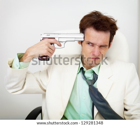 Tattered business man in white suit keeps gun near his temple on black background