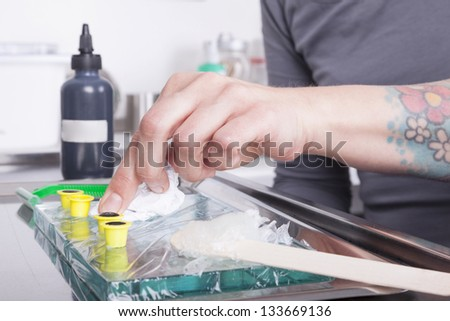 tattoo artist at work. ( property release supplied includes tattooists' tattoo and artwork ) - stock photo