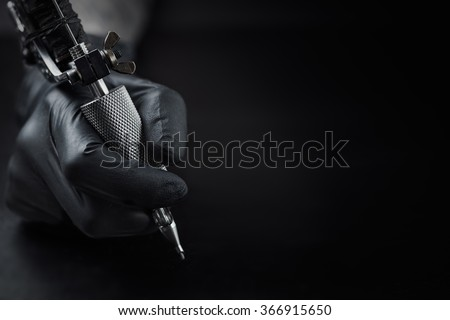 Tattoo artist holding tattoo machine on dark background with space for text