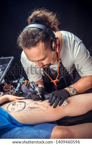 Tattoo artist makes tattoo pictures in tattoo studio