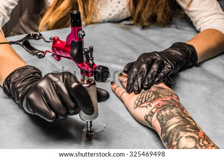 Tattoo artist takes an orange paint for black and red tattoo which draws for a girl. Master works in a professional salon with pink tattoo machine on a blue mat and in sterile  black gloves.