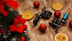 Tattoo machines on a christmas background - christmas decor with tree on a wooden background