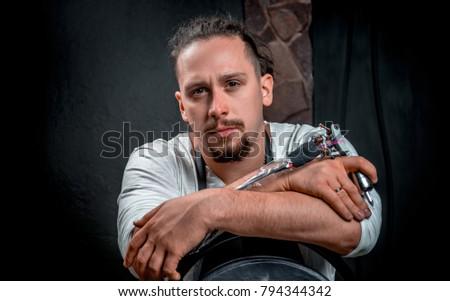 Tattoo master and a tattoo machine in tattoo parlor #794344342