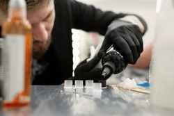 Tattoo master pours black paint. Tattoo artist prepares tools and ink before working in a tattoo parlor.