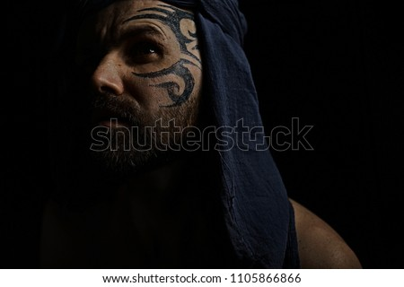 Stock Photo tattoo on the face,  male portrait in the form of an assassin, cosplay,  tattooed brutal man,  guy with a tattooed face