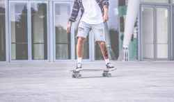 Tattoo skater performing with longboard in urban city contest with offices in background - Young trendy man having fun with skateboard - Extreme sport concept - Focus on feet shoes