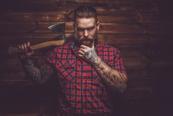Tattooed  bearded male in a blue shirt posing over wooden wall in a studio.
