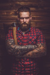 Tattooed  bearded maleholding axe and posing over wooden wall in a studio.