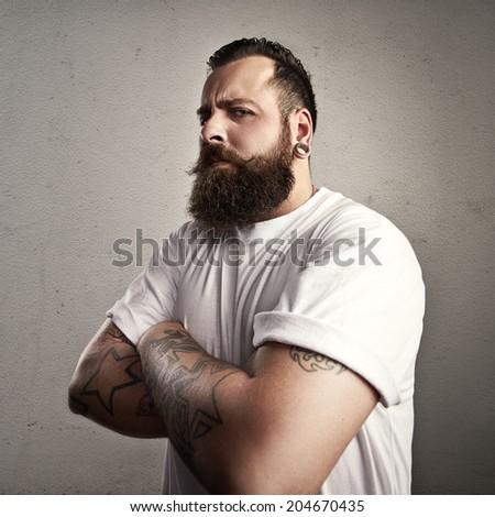 Tattooed bearded man wearing white t-shirt