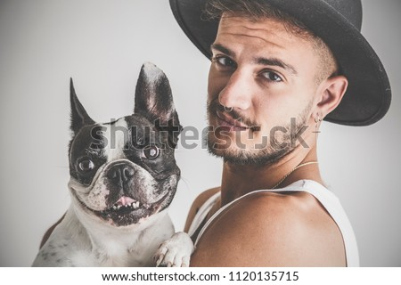 Tattooed boy with piercings with French Bulldog dog in his arms on white background
