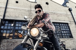 Tattooed cool young man with sunglasses sitting on vintage motorcycle