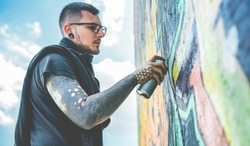 Tattooed graffiti writer painting with color spray his dark picture on the wall - Contemporary artist at work - Urban lifestyle,street art concept