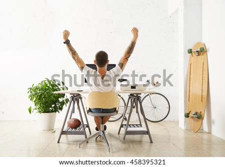 Tattooed lucky freelancer in front of his working space, surrounded with his hobby toys longboard, vintage bicycle and green plant, stretching his hand in air while making break