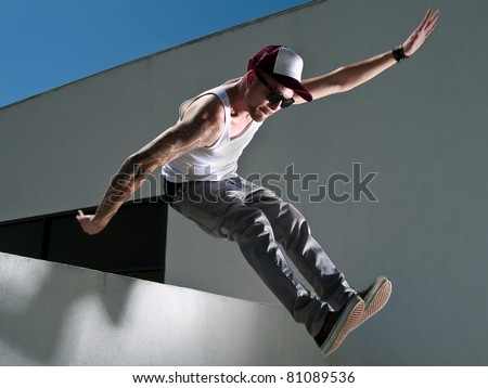 tattooed male parkour free runner jumping off a building - stock photo