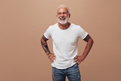 Tattooed man in good mood posing on beige background. Gray-haired guy in white T-shirt and blue jeans laughs into camera