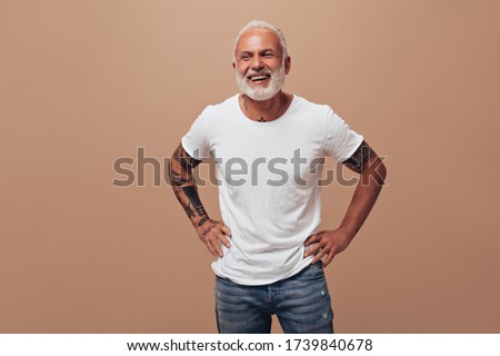 Tattooed man in good mood posing on beige background. Gray-haired guy in white T-shirt and blue jeans laughs into camera Stock fotó ©