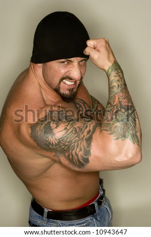 stock photo : Tattooed man posing with flexed biceps.