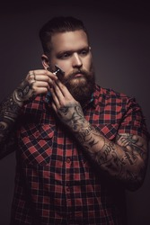 Tattooed man with beard  in red t shirt  holding safety razor. Isolated on grey background.