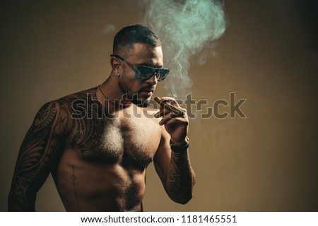 Tattooed man with cigar. Cigar smoking enjoy life and moment. Portrait of a bearded businessman with a beautiful torso smoking a cigar and drinking whiskey.