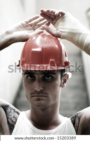 tattooed man with red helmet and hand in plaster