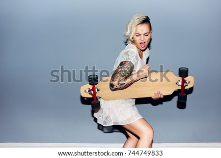 Tattooed pretty blond girl goofing around, playing longboard as guitar and singing ストックフォト ©