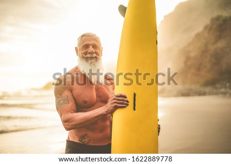 Tattooed senior surfer holding surf board on the beach at sunset - Happy old guy having fun doing extreme sport - Joyful elderly concept - Focus on his face Сток-фото ©