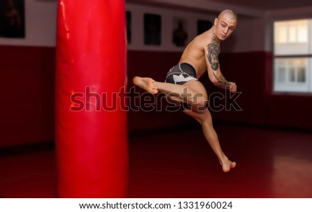 Tattooed young MMA fighter in a jump with a turn kicks a bag with his foot. Mixed martial arts training in a gym. Preparations before fight. Bold man with tattoos fights. Brutal and spectacular punch