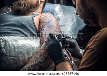 e41baac08 Tattooist at work in studio./Professional tattoo artist makes cool tattoo  in salon.