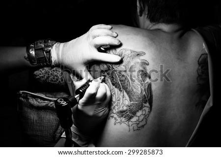 Tattooist making by professional artist is tattooing body sexy woman using machine in a creative design work studio. Process decoration ink artwork female skin koi fish pattern. #299285873