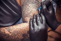 Tattooist posing in tatoo salon.