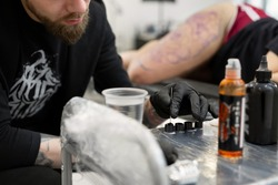 Tattooist stirs the black paint. Tattoo artist prepares tools and ink before working in a tattoo parlor.