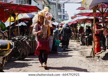TAUNGGYI, MYANMAR - FEB 8: A Burmese street vendor walks around selling food at Taunggyi market in Myanmar on Feb 8, 2017. #664792921