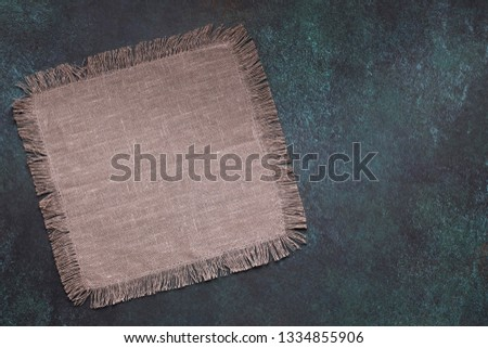 Taupe napkin on dark grunge table top view with copy space #1334855906