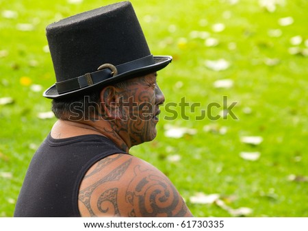 TAURANGA, NEW ZEALAND - APRIL 3: Maori male watching musicians on outdoor stage on April 3, 2010 in Tauranga, New Zealand. Maori activist Tama Iti wears hat and traditional moko or facial tattoos.