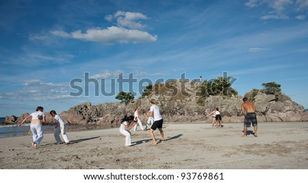TAURANGA, NEW ZEALAND - JANUARY 23: Group of youths practice capoeira on the Mount Maunganui beach, Tauranga New Zealand on January 23 2012. Founded in Brazil in 1984.